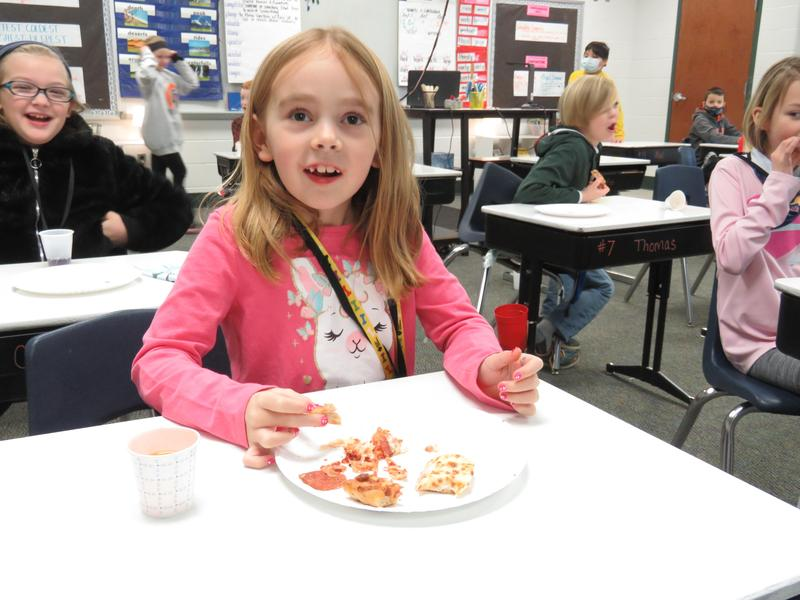 A Lee 3rd-grader enjoys Little Caesars Pizza during the Taste of Michigan lesson.