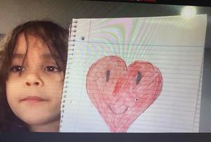 Student holding notebook with heart drawing