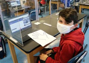 """As part of Cultural Diversity Day, 6th grader Matthew Logozzo and other students at Edison Intermediate School used a paper cutout of a hand to list five characteristics, comparing and connecting with the """"hands"""" of students who share commonalities."""