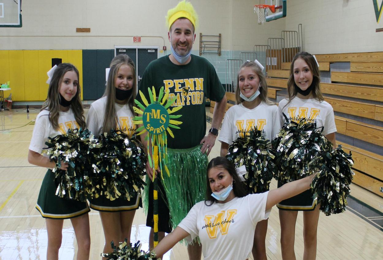 Students pose with a teacher at a pep-rally
