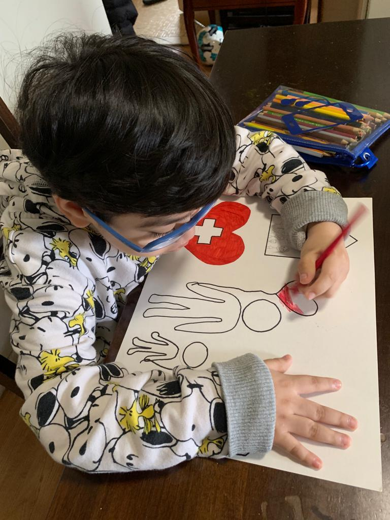 boy with glasses drawing his poster
