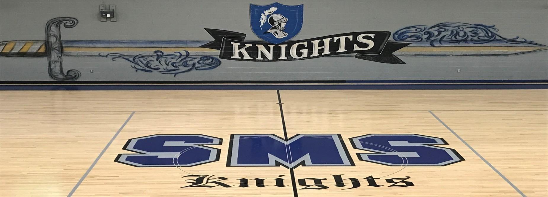 Gym floor with school logo and sword with Knights Shield on wall