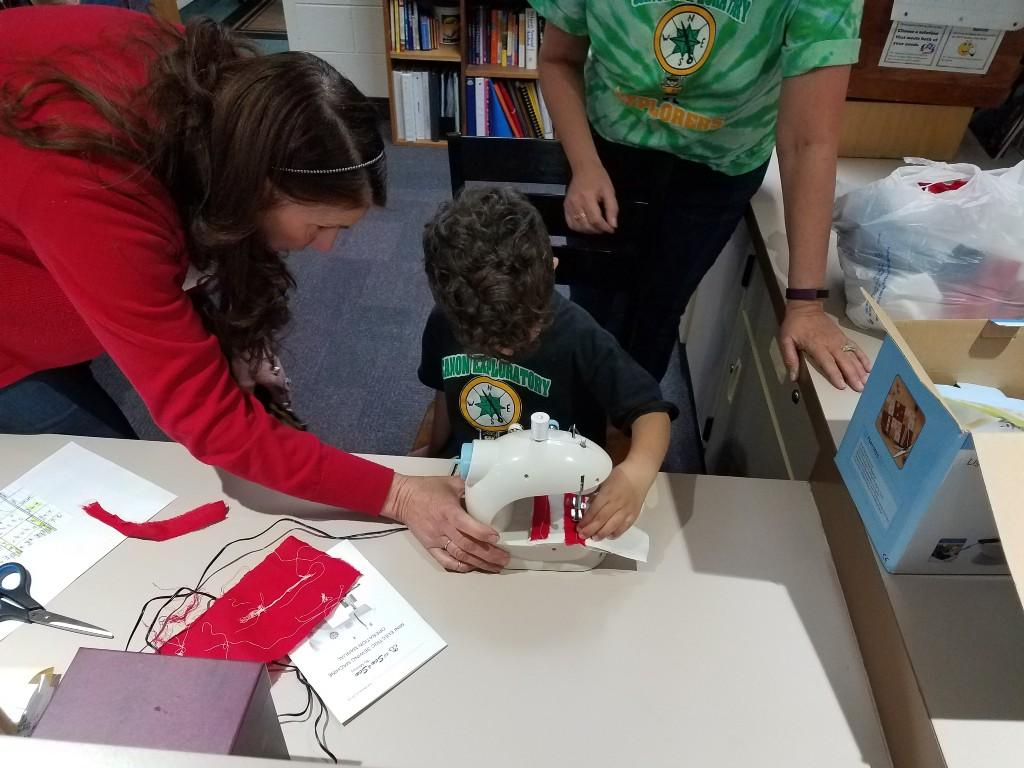 Kindergartner learns how to use a sewing machine.