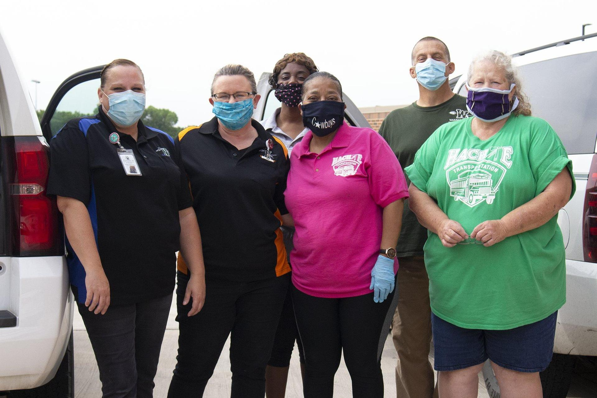bus drivers posing together wearing face masks
