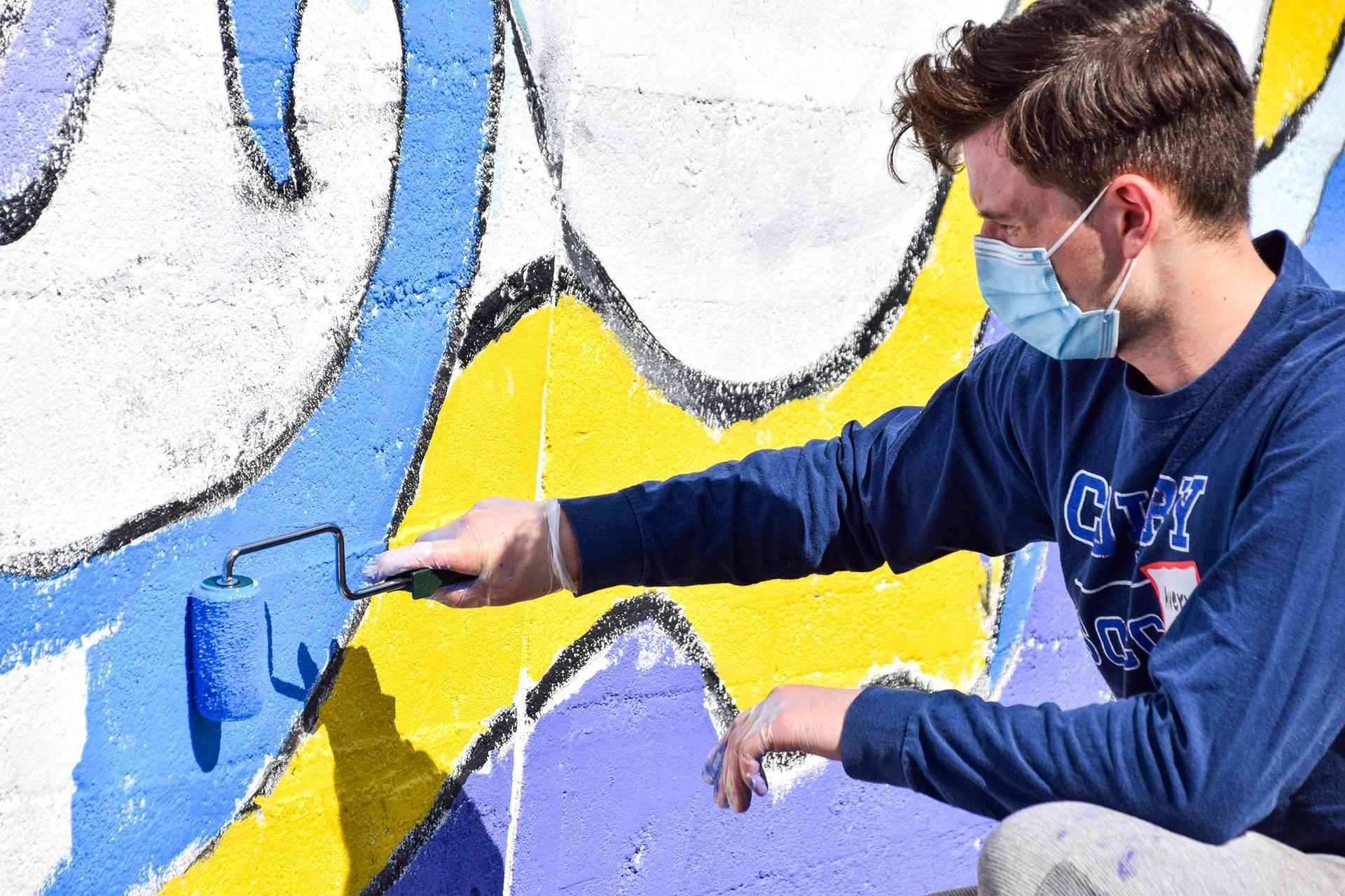 A person paints part of a mural on a wall