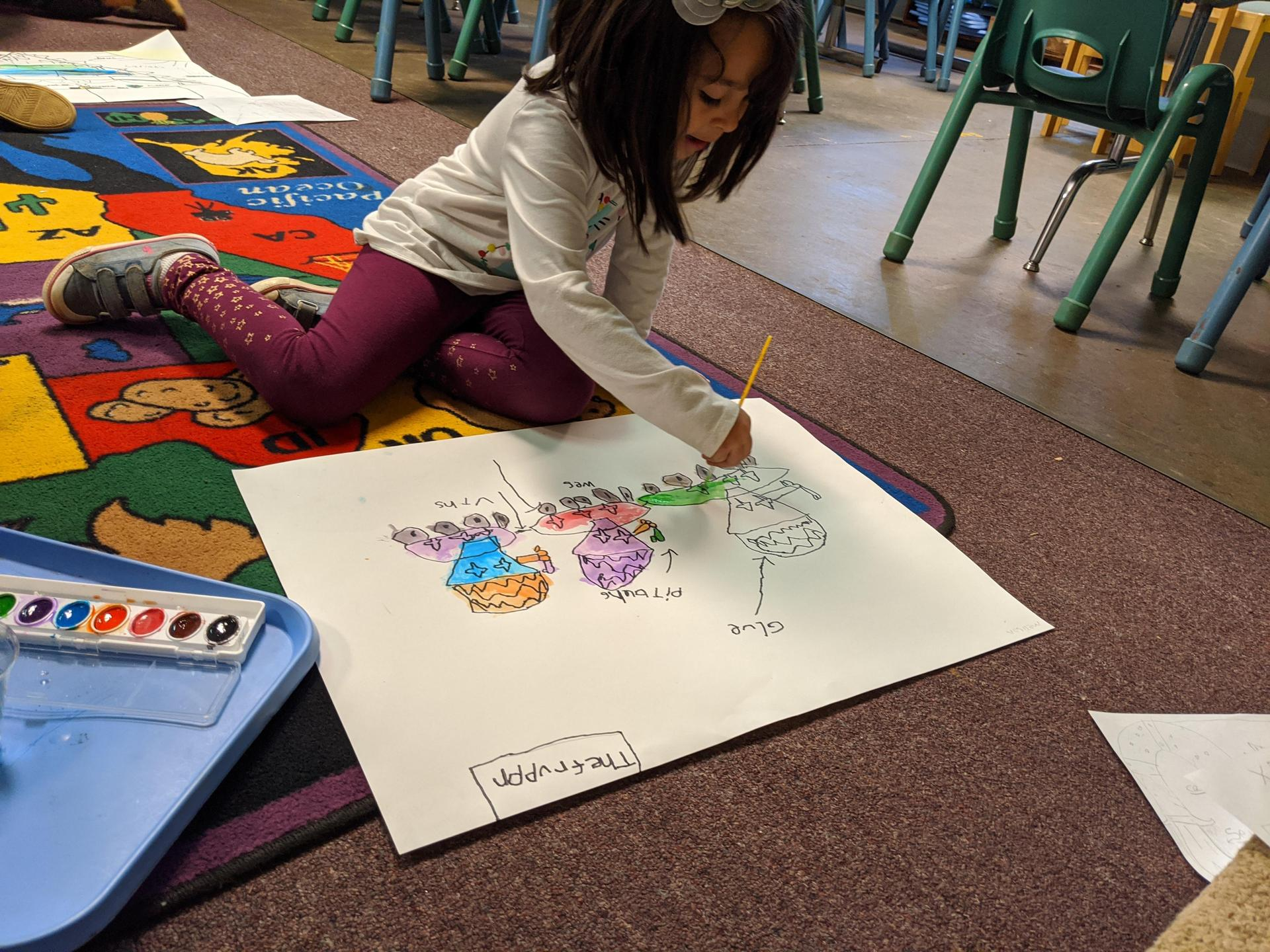 A student sits on the floor and colors.