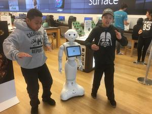 two students dancing with a small robot in a store