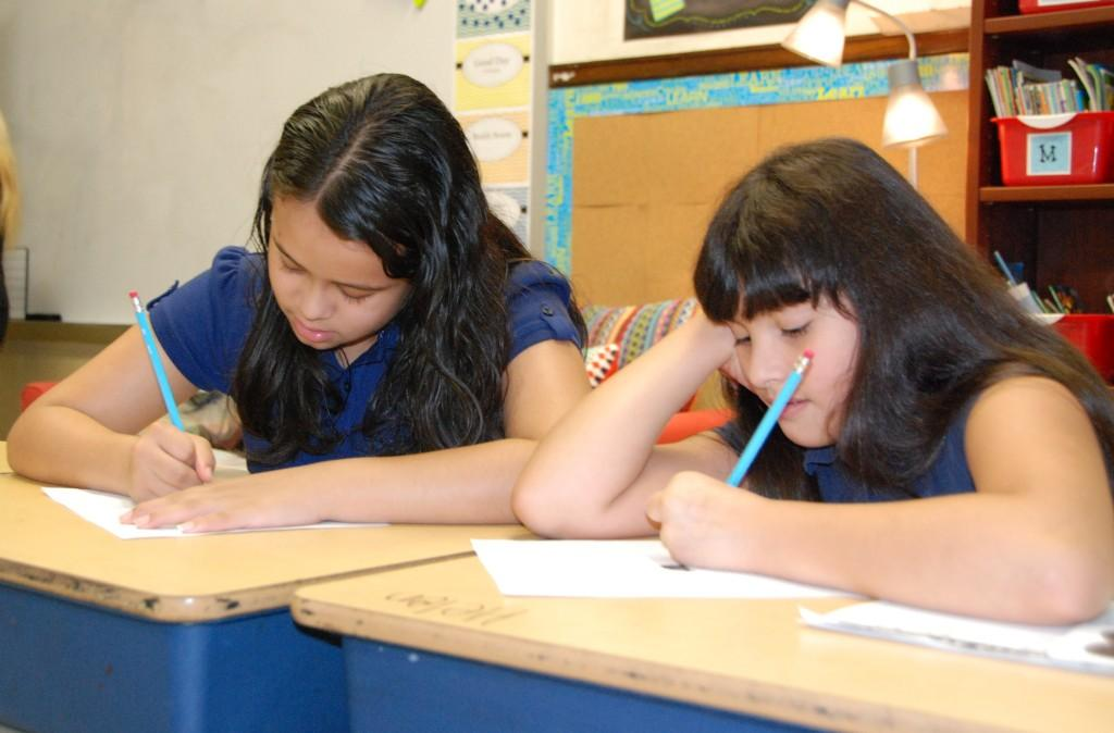 Girls at desks, writing, first day of school 2016-17