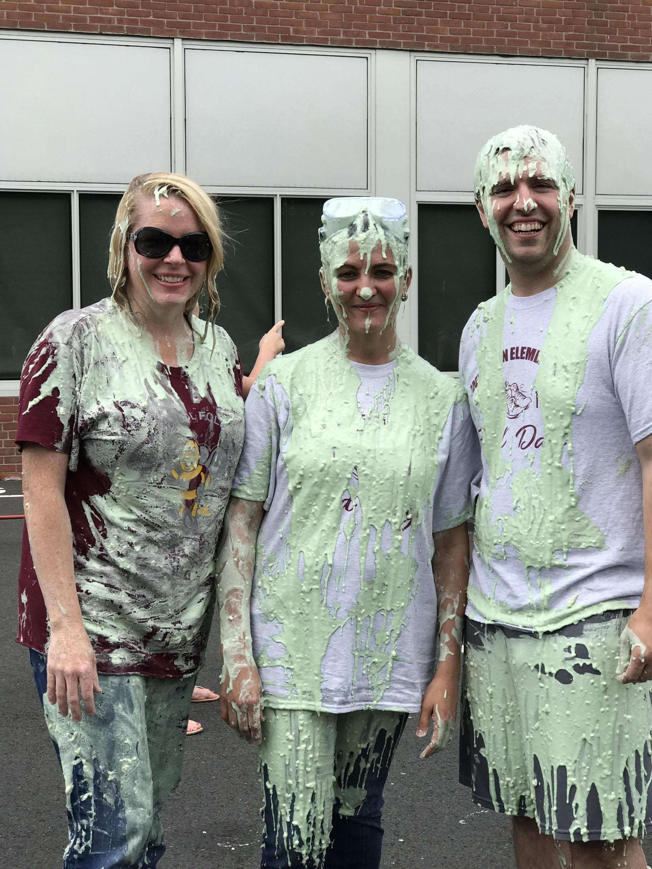 Three teachers are covered in slime.