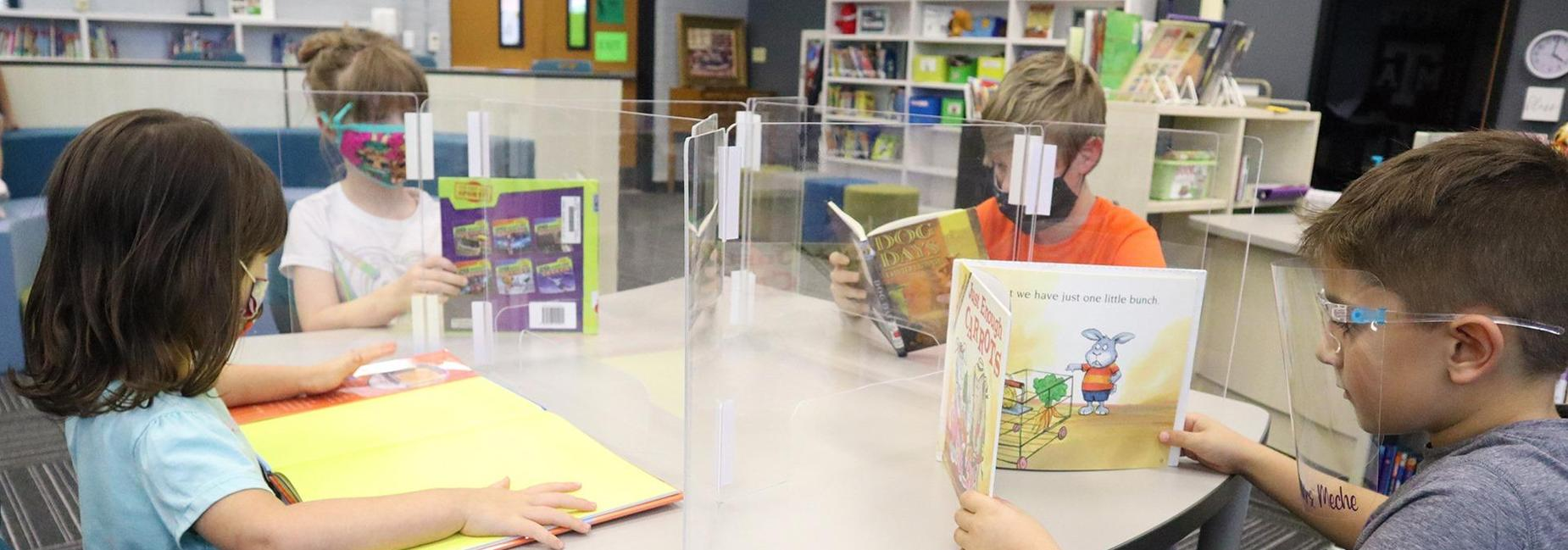 4 students reading, wearing face shields face each other  with plexiglass shields between them
