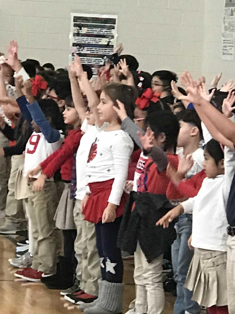 group of children raising their hands while singing