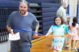 a dad and daughter racing with hula hoops