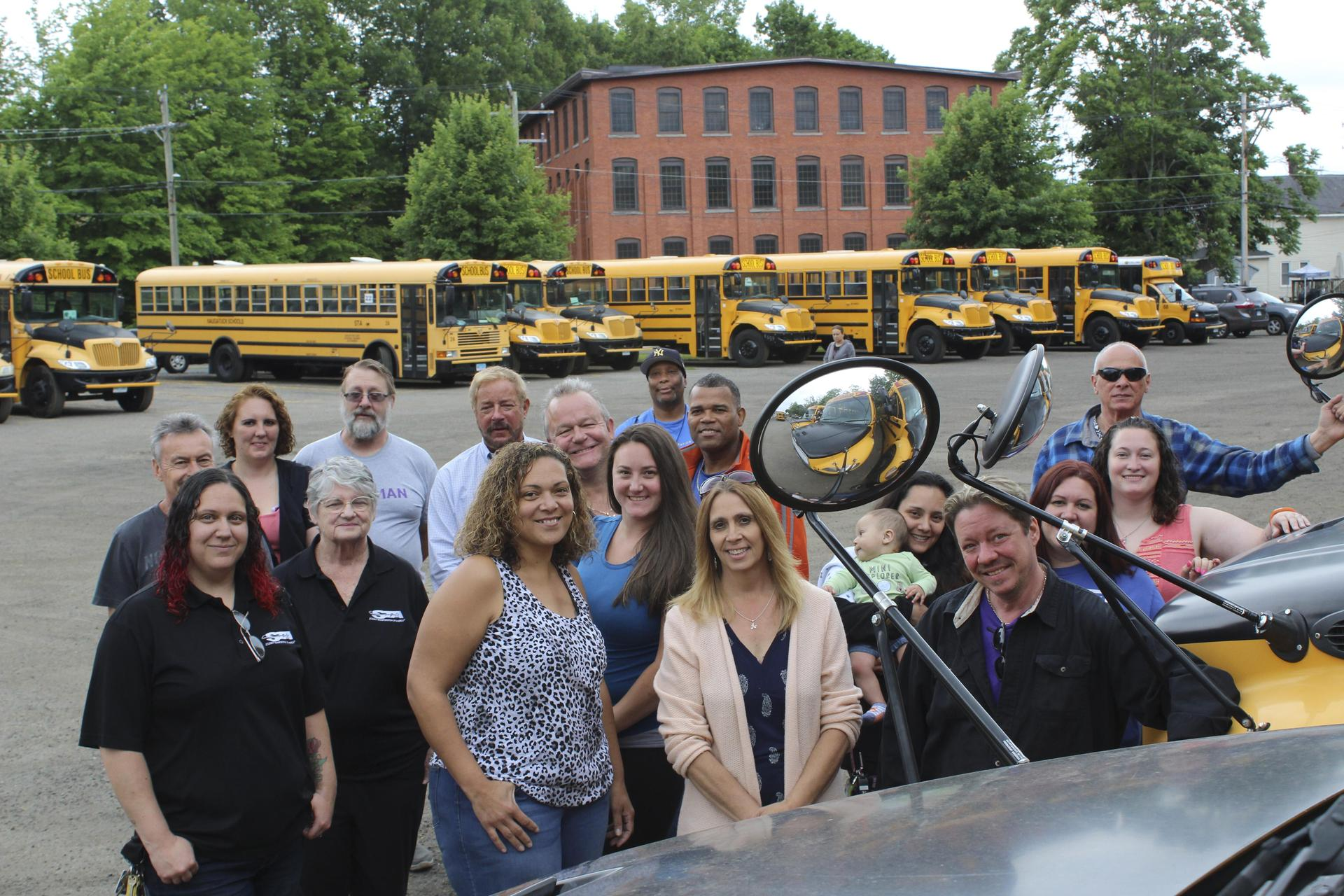 Bus drivers posing in front of busses