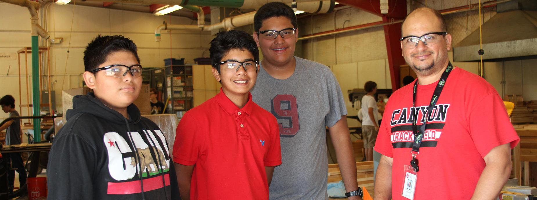 Teacher and students standing in the  wood shop