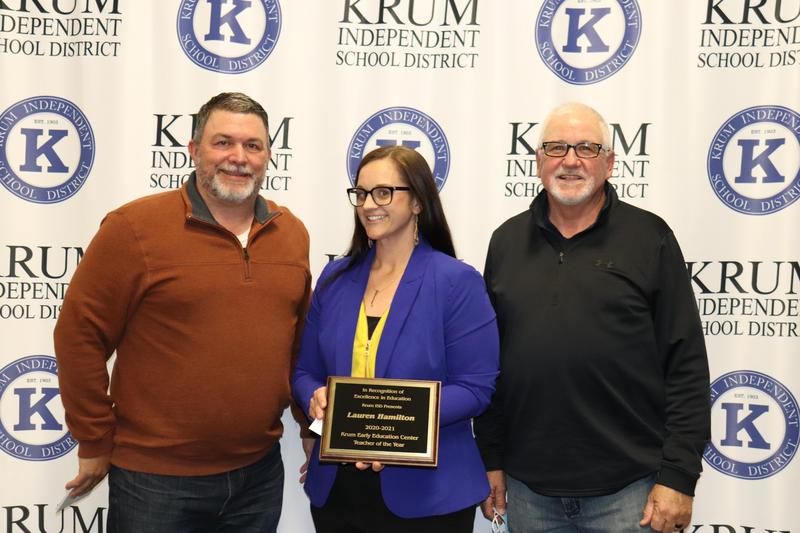 lauren hamilton stands with board president eric borchardt and board vp terry knight as they present her with her teacher of the year plaque