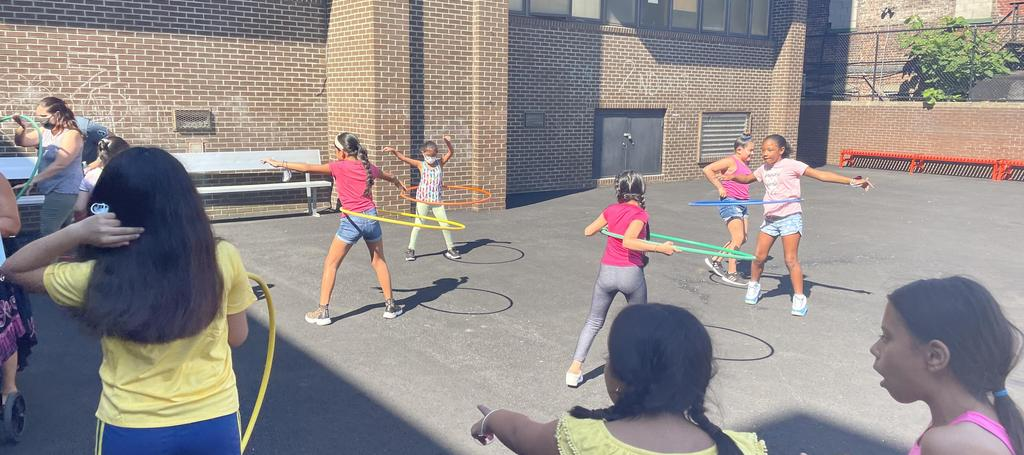 Students hula hooping on outside court