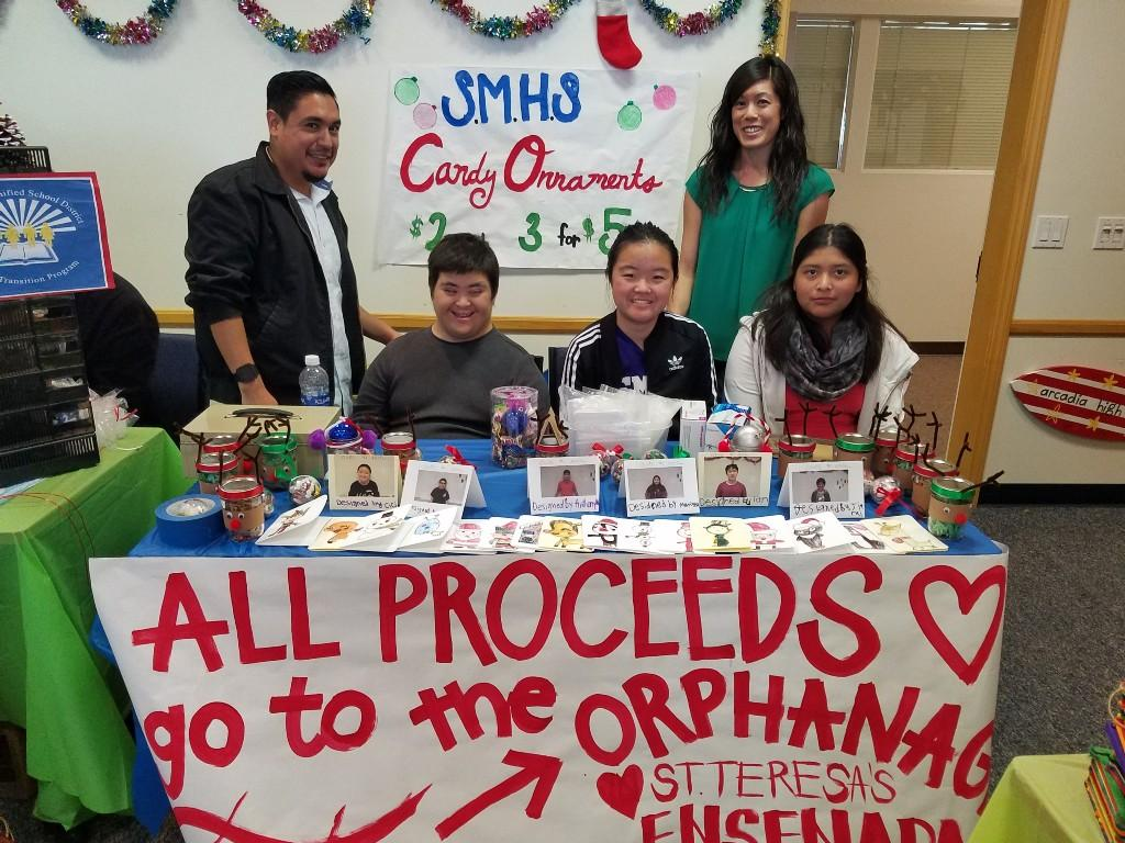 Students sitting at table selling crafts