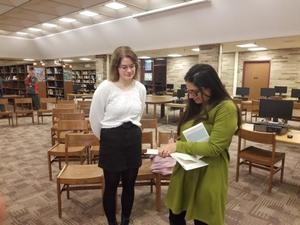 Student with an author who is signing her book