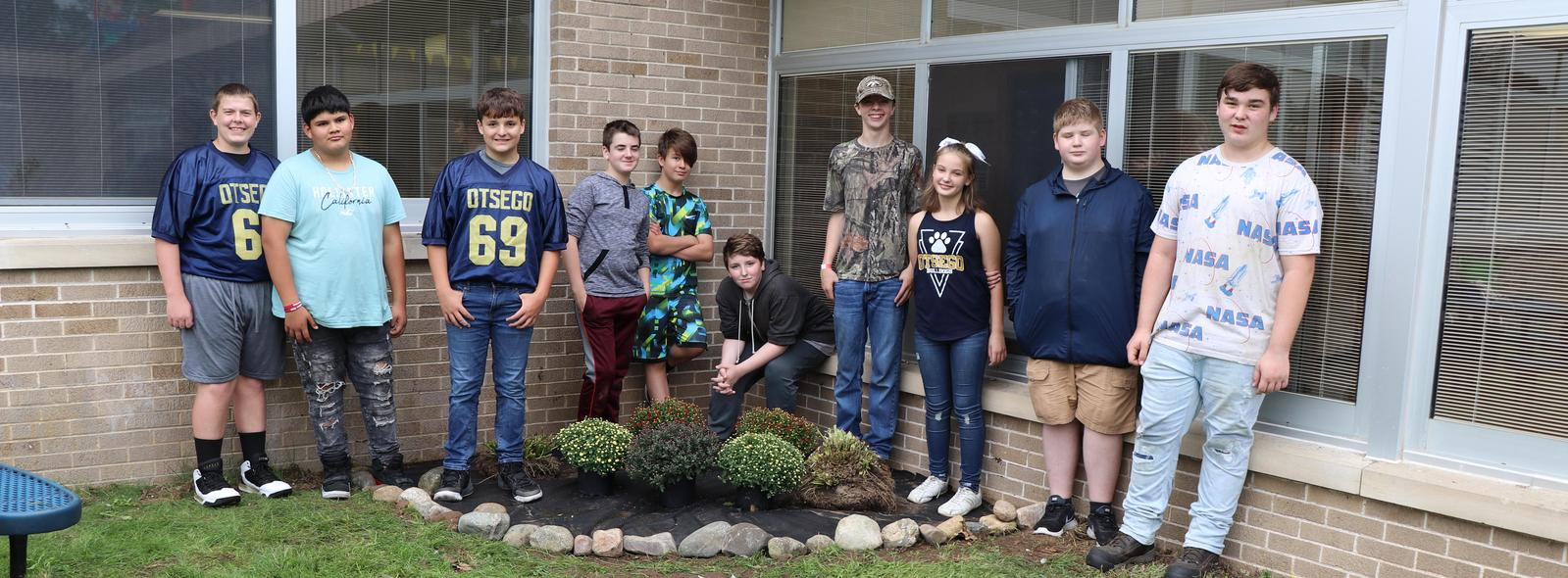 Students by the flower bed they planted in the courtyard.