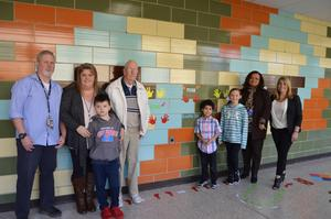 Teachers Mr. Winters, Ms. Hill, Principal Mrs. Toller, 3 students, and Dr. Velazquez line up in front of the Sensory Wall