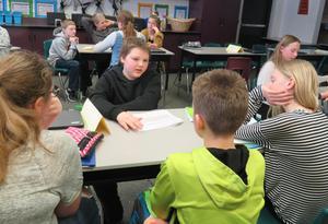 Clayton Mohr discusses his speeh topic with classmates.