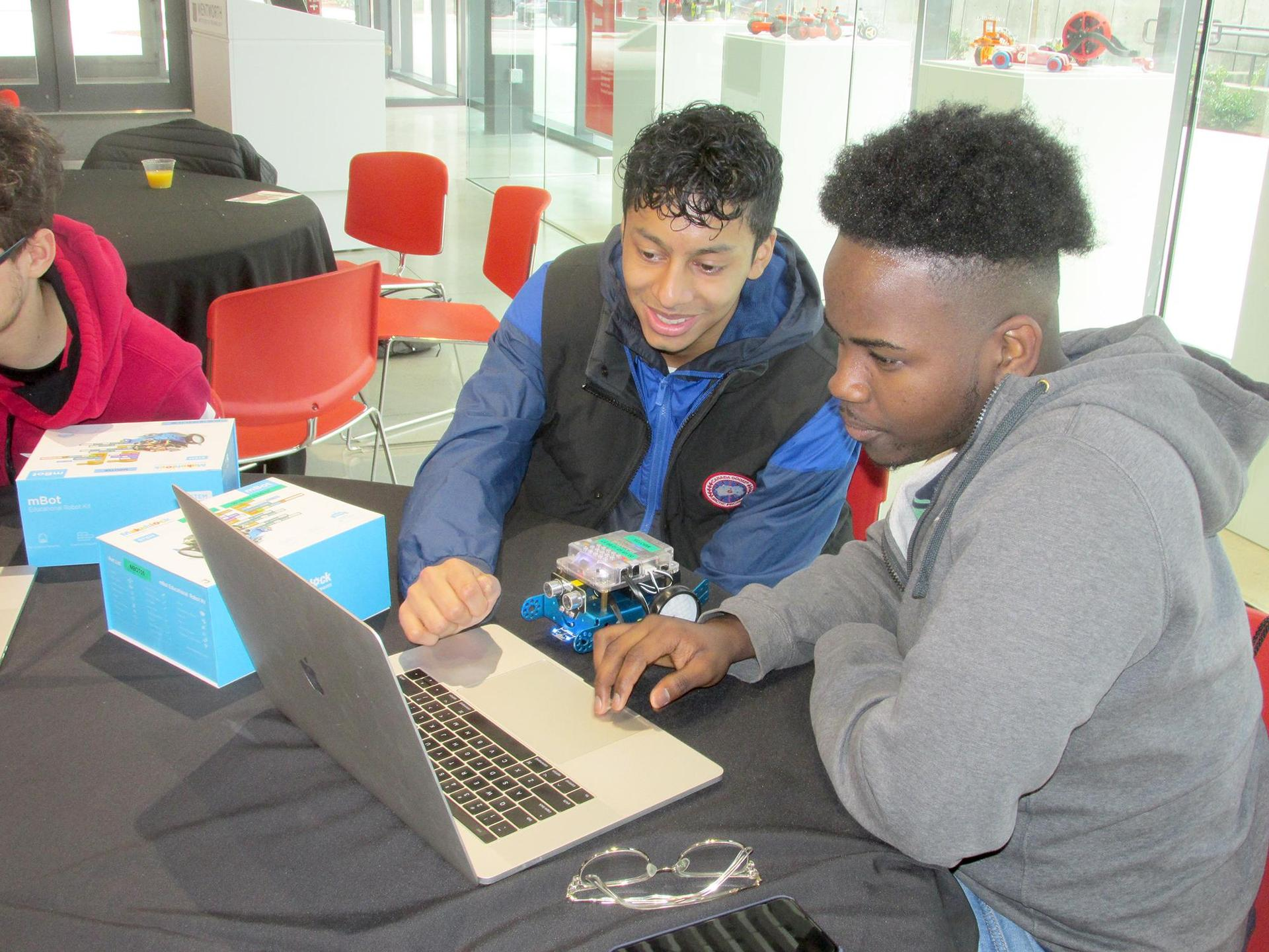 Two students looking at a laptop screen