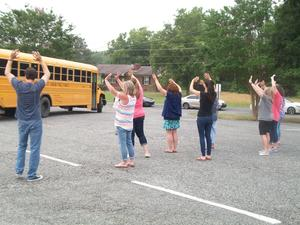 Staff members wave goodbye as the buses leave.
