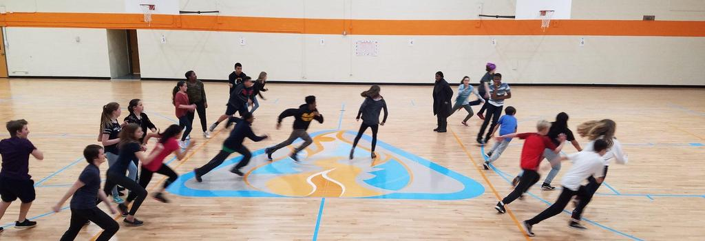 students playing a game in the gym with the school logo in the center of the floor