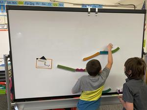 A magnetic white board gives students a chance to design and build marble runs.