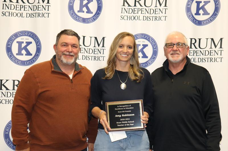 amy robinson stands with board president eric borchardt and board vp terry knight as they present her with her teacher of the year plaque