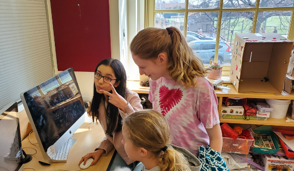 3 girls playing a coding game together at a computer.