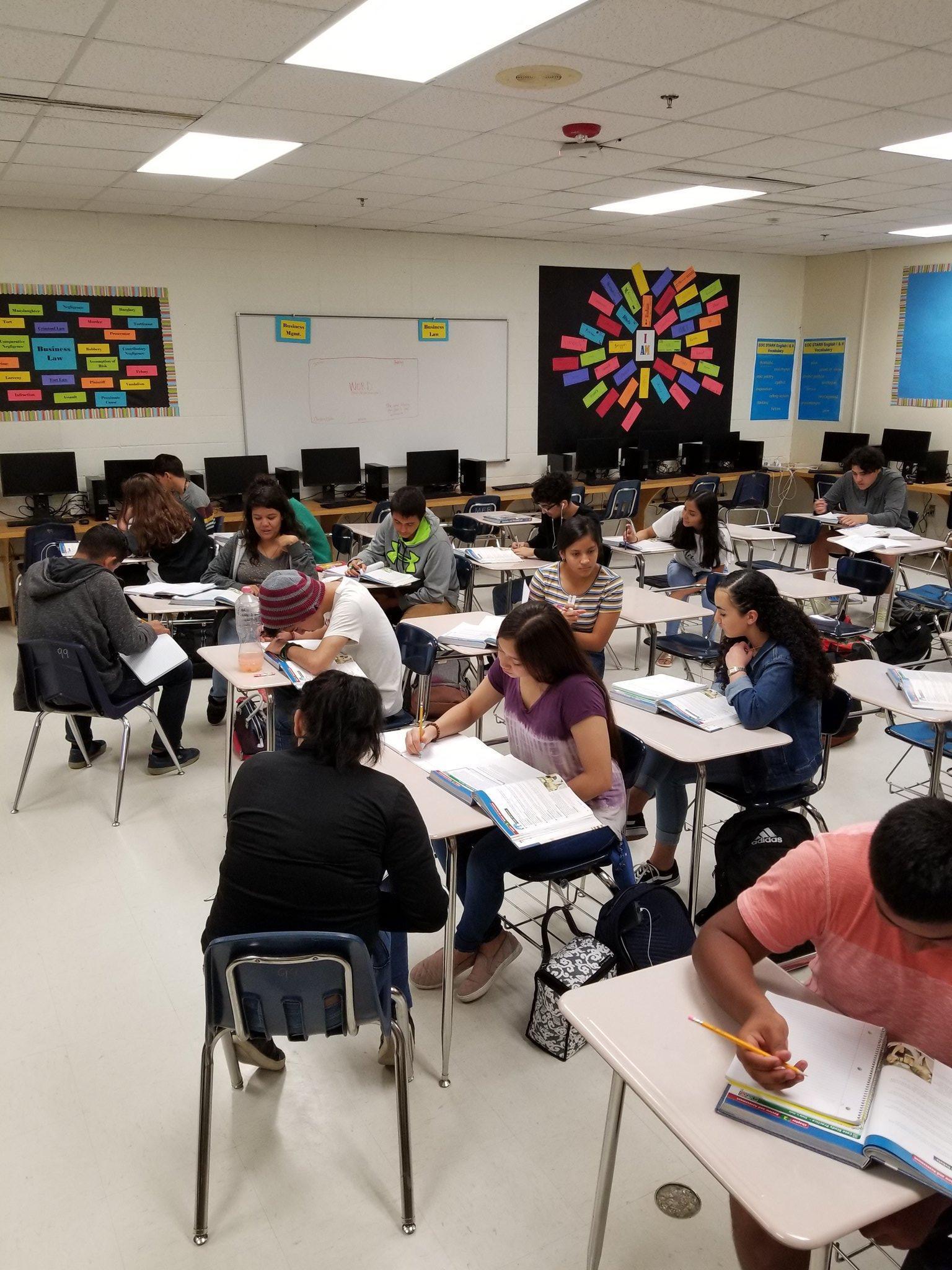 students sitting in desks completing work