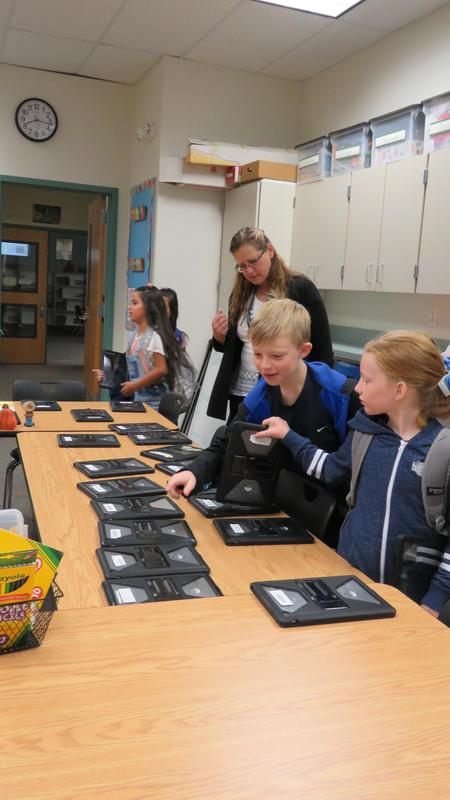 Students pick up their iPads before the Donut Hackers meeting begins.