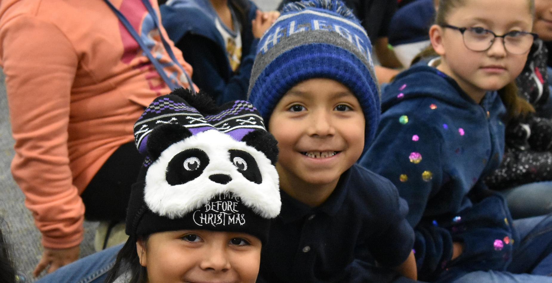 A little girl wearing a panda hat, and a boy wearing a blue stocking hat for hat day.