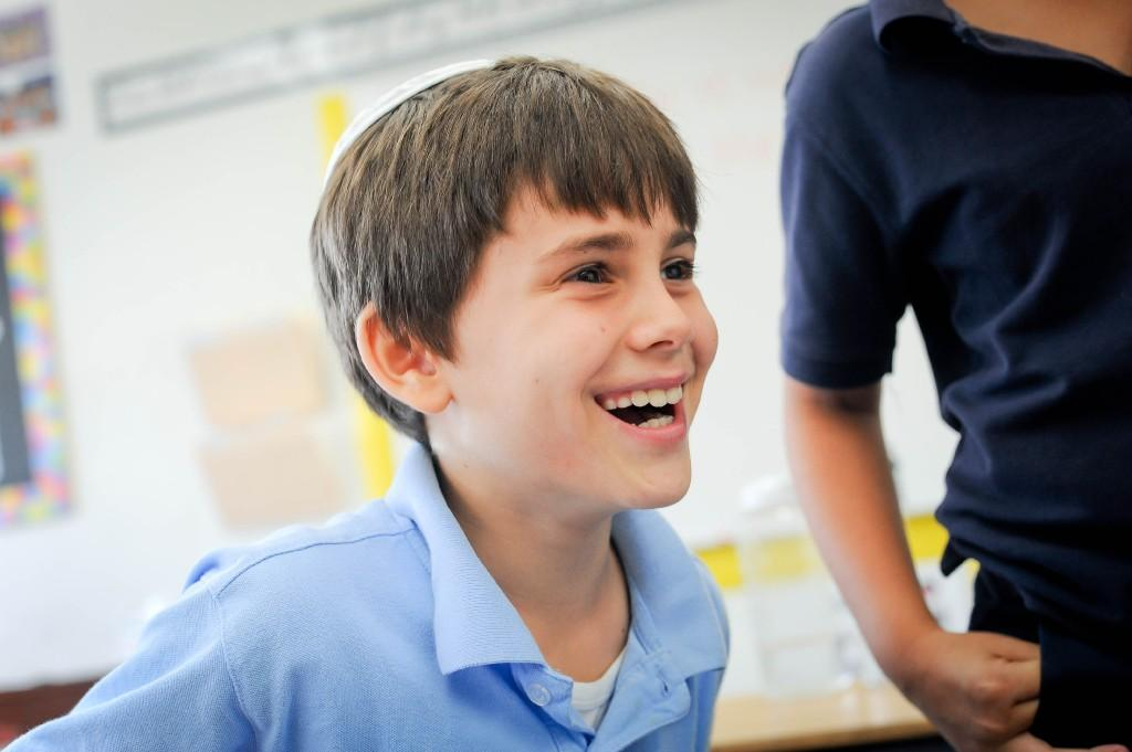 boy smiling in a classroom