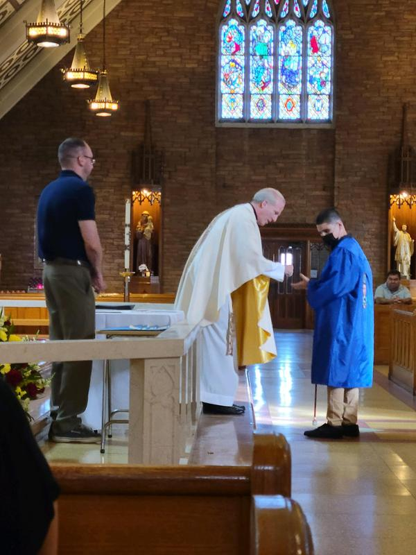 Yadiel receives his diploma from Fr. Tom.