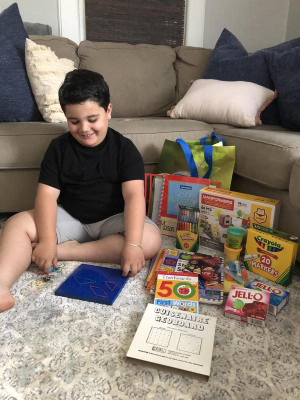 boy with coloring supplies and books