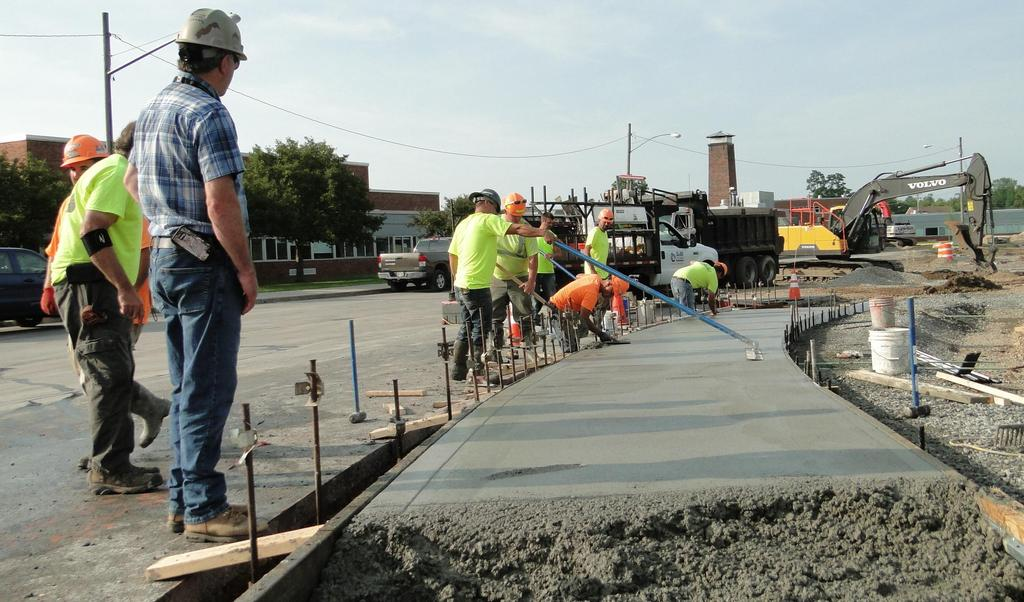 Site construction workers construct a concrete sidewalk near the new bus loop