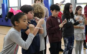 A photo of Tamaques 5th graders trying to blow a small object into a heart-shaped container, one of the fun activities planned on Valentine's Day.