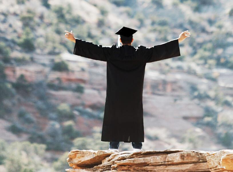 student in cap and gown on hilltop
