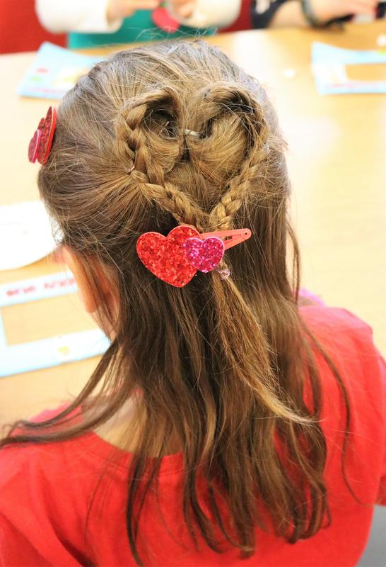 Photo of the back of the head of a kindergartner whose hair is braided and shaped into a heart for Valentine's Day.