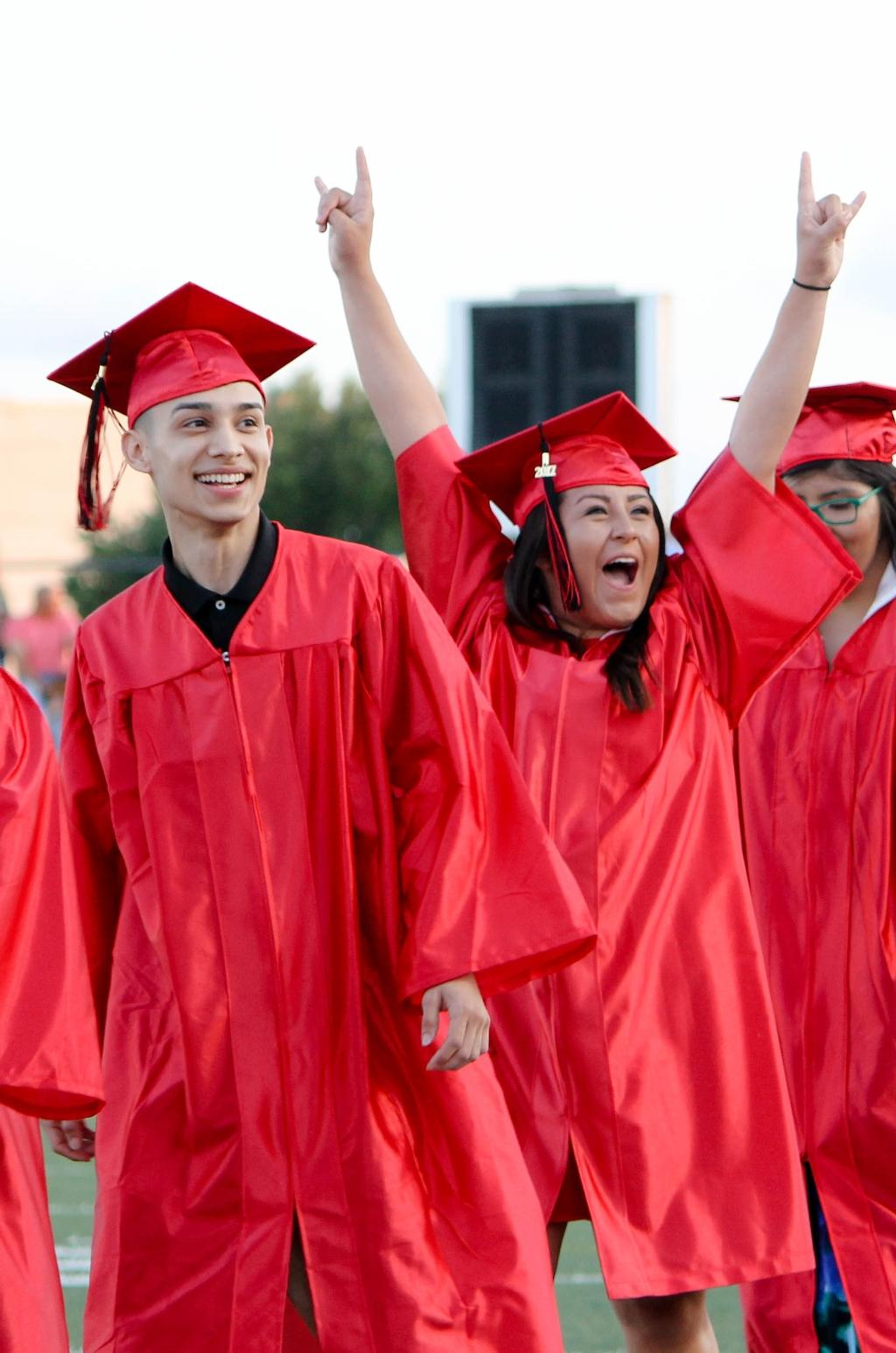 students of the victoria east high school 2018 graduating walking into memorial stadium, smiling male student and a smiling female student screaming with excitement and rockstar hands in the air