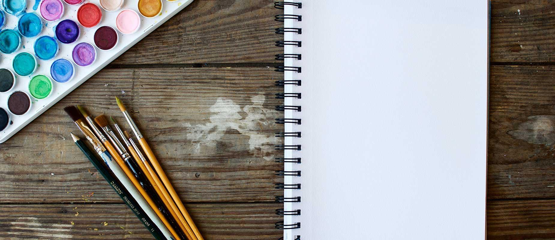Notebook and watercolor supplies on a table