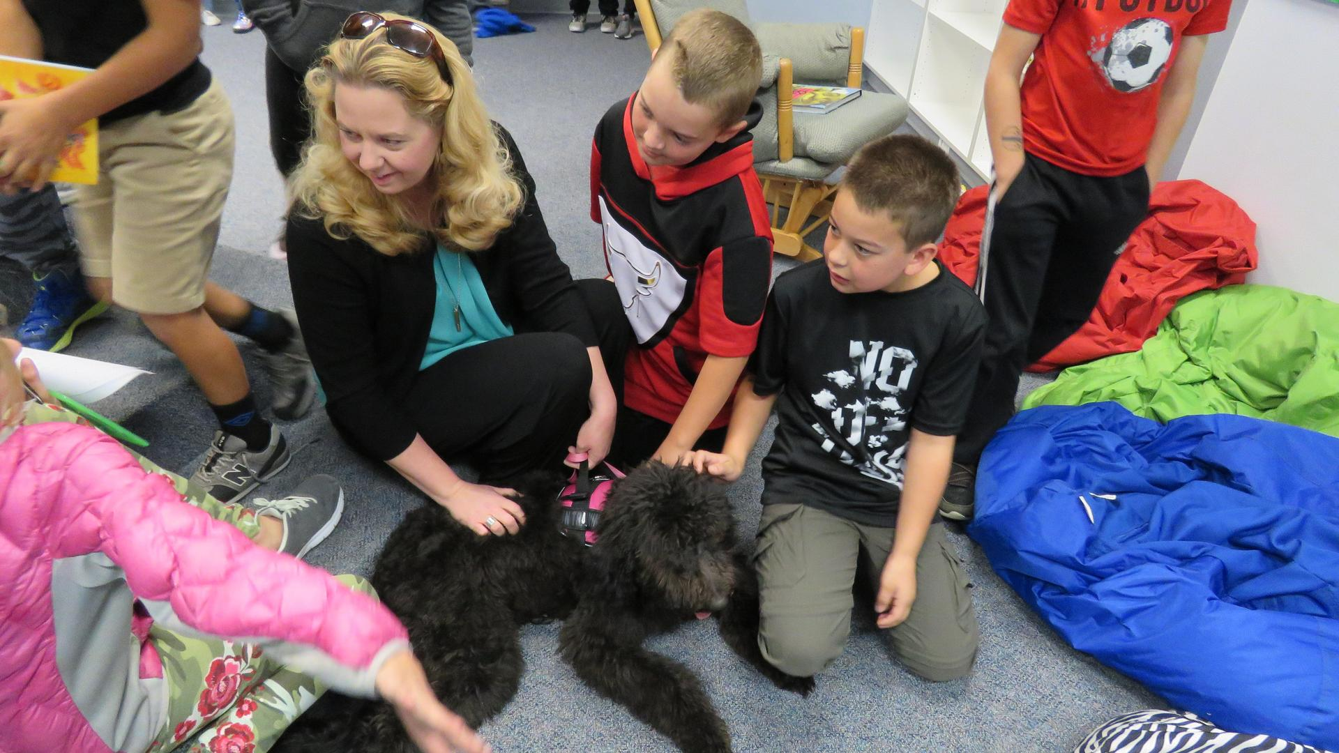 Shawn Tegethoff and kids play with a therapy dog at Roosevelt.