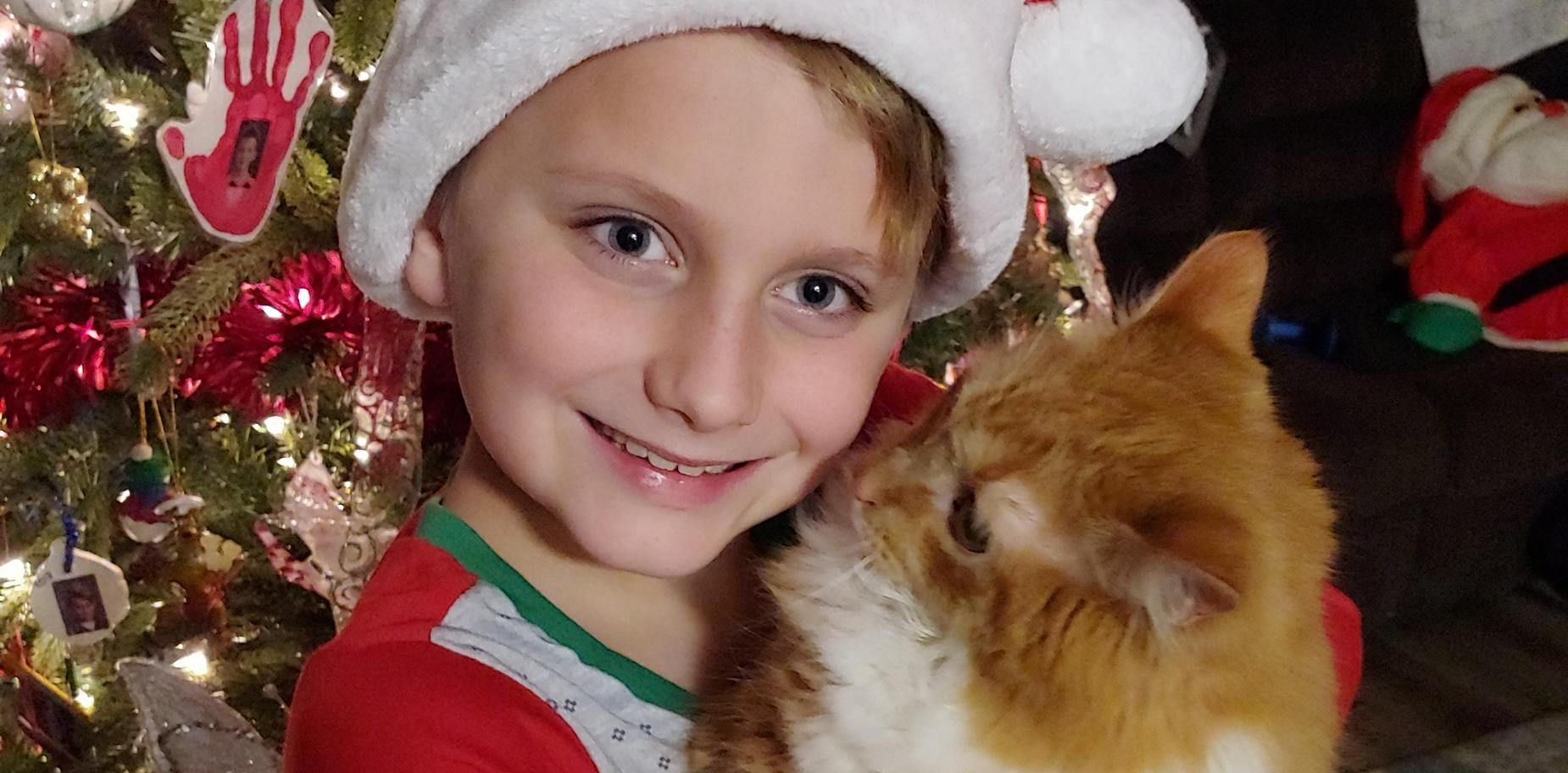 boy in holiday attire with his cat