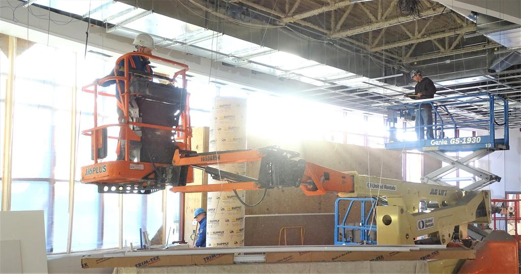 This snapshot from late in November 2019 shows construction crew members on an orange articulated boom lift and a blue scissors lift within the soon-to-be-completed large group instruction room that will also be called the Learning Theater. There is substantial construction work within the high ceiling areas of that new program space.