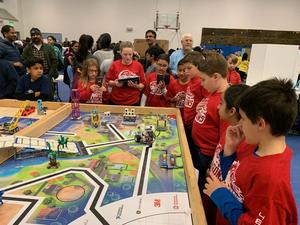 Team members wearing red t-shirts standing at the competition table while their robot travels around the course