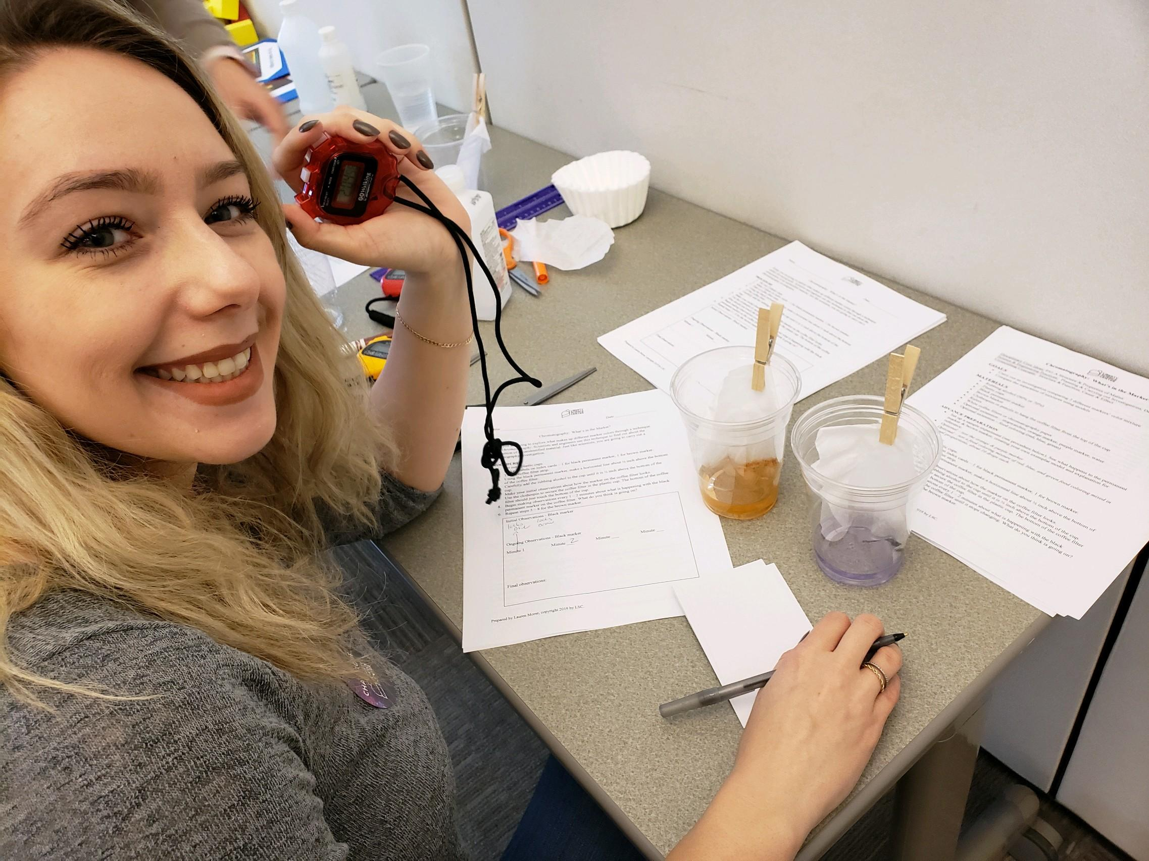 female teacher holding a stop watch to observe two liquids and recording data