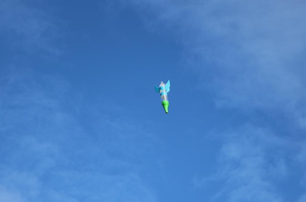 Photo of handmade rocket in air.