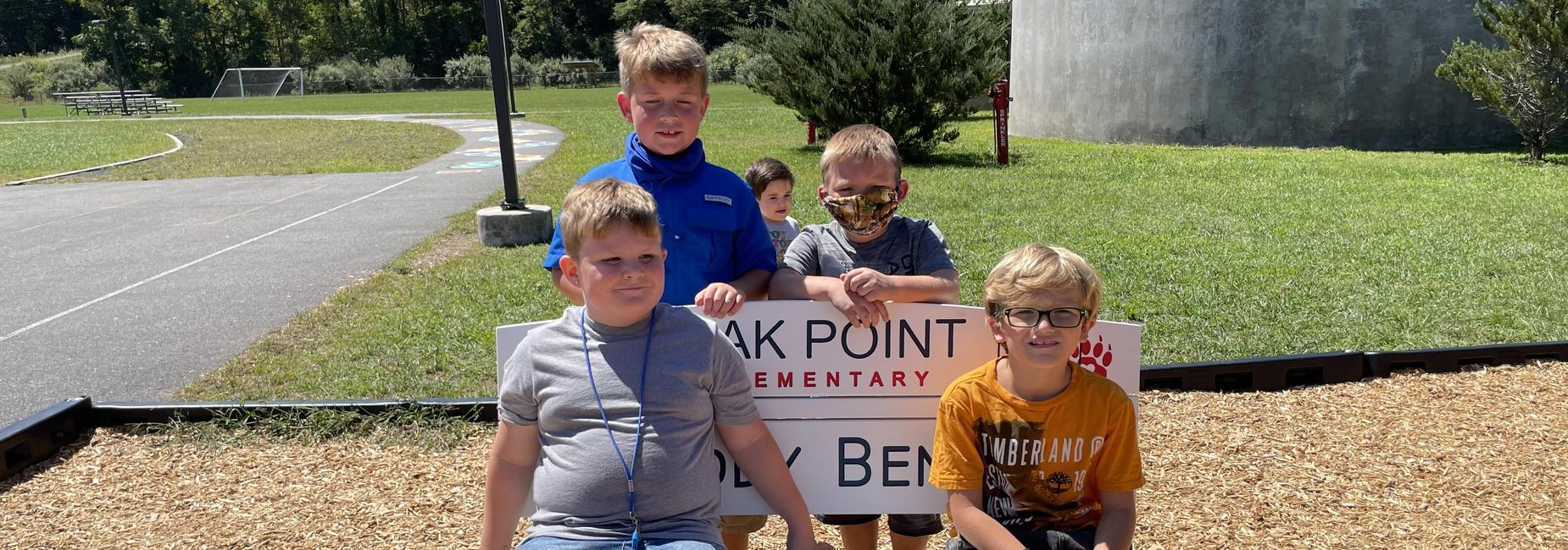 Photo of Oak Point students sitting on the new Buddy Bench on the playground